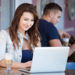 Portrait of happy smiling beautiful young woman sitting in street cafe with glass of drink on the table, using laptop, looking at the screen, male customer on the background